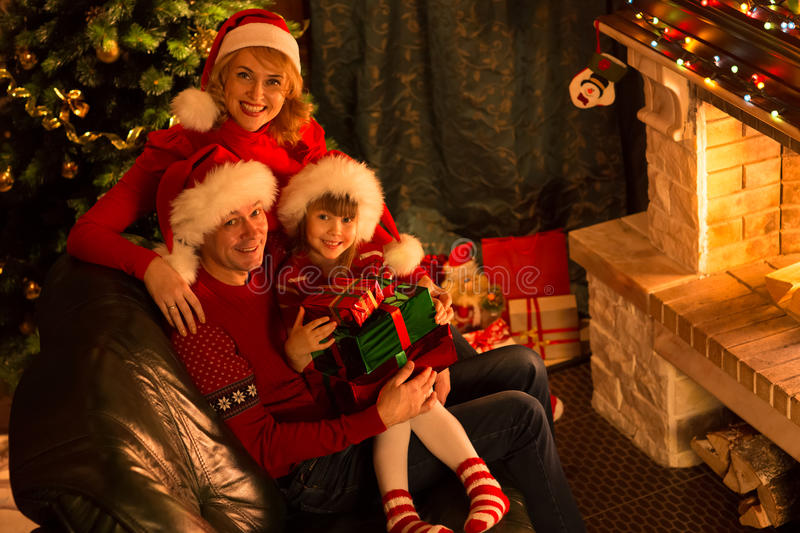 Happy family in red hats with gifts sitting at. Happy family in Santa hats with gifts sitting at Christmas tree near fireplace stock photos