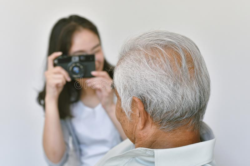 Happy family relationship, Asian daughter taking photo of old elderly father to keep good memory. Happy family relationship, Asian daughter taking photo of old stock photography