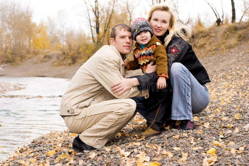 Happy family relaxing near the lake. Happy young family walking near the lake royalty free stock photography