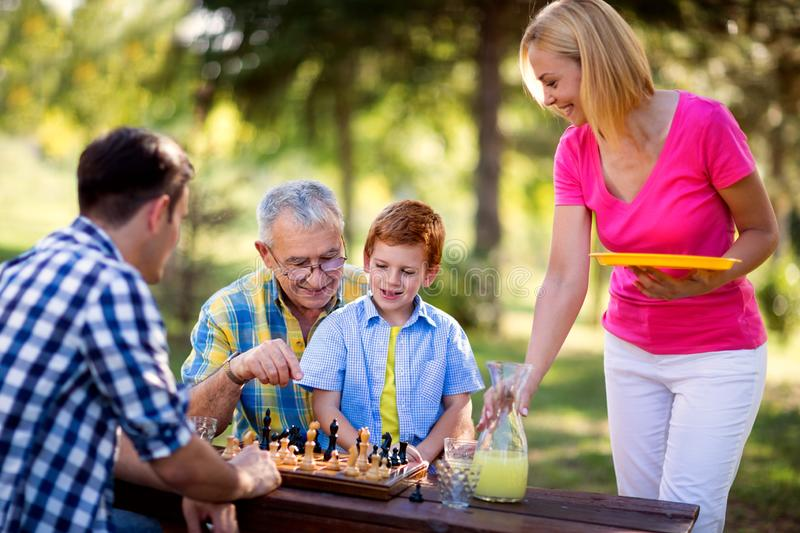 Happy family relaxing playing chess. In the park royalty free stock photos