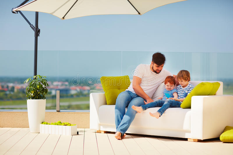 Happy family relaxing on roof top terrace at warm sunny day stock photo