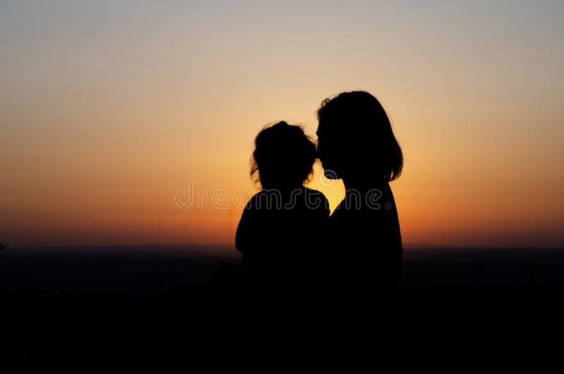 Mother and daughter relaxing at sunset stock image