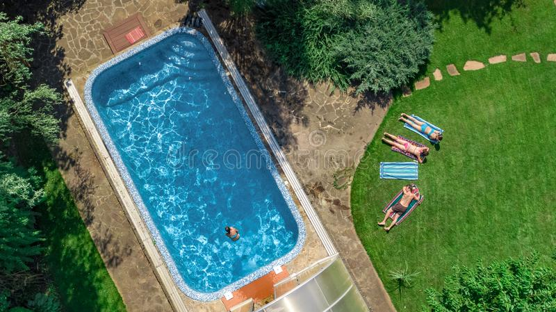 Happy family relaxing by swimming pool, aerial drone view from above of parents and kids have fun on vacation, family weekend royalty free stock images