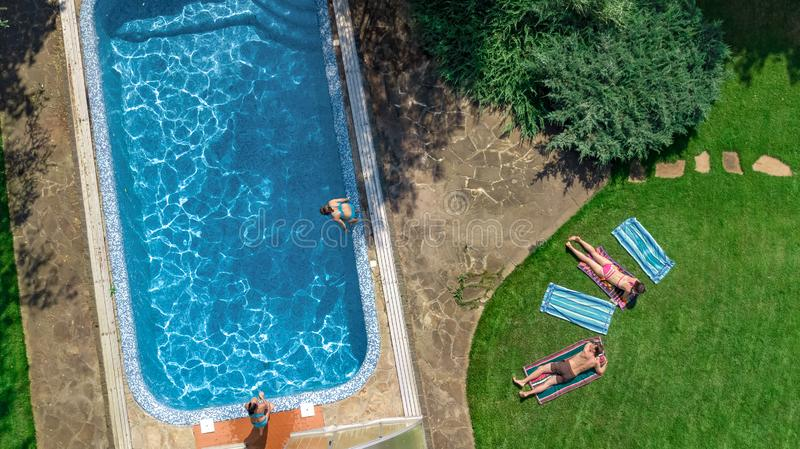 Happy family relaxing by swimming pool, aerial drone view from above of parents and kids have fun on vacation, family weekend. On resort royalty free stock photos