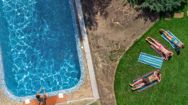 Happy family relaxing by swimming pool, aerial drone view from above of parents and kids have fun on vacation, family weekend. On resort royalty free stock image