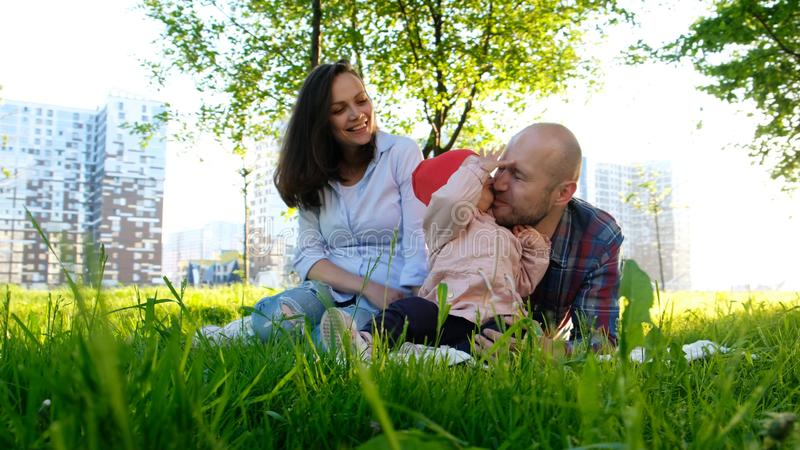 Happy family is resting on nature. Parents play with a small child daughter in a park in the summer at sunset. royalty free stock image