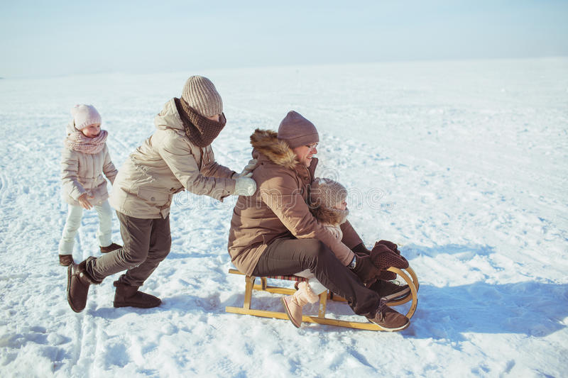 Happy family ride on a sledge in winter stock photos
