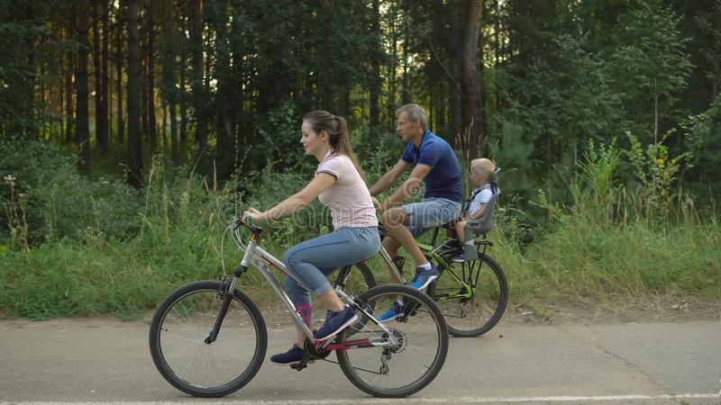 Happy family rides on bicycles in the forest stock photography