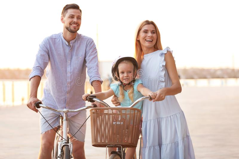 Happy family riding bicycles outdoors stock photo