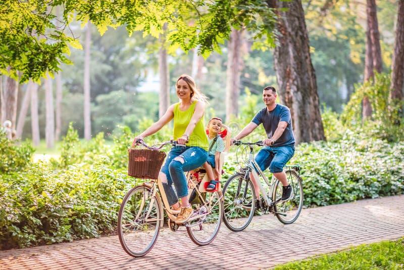 Happy family is riding bikes outdoors stock photo