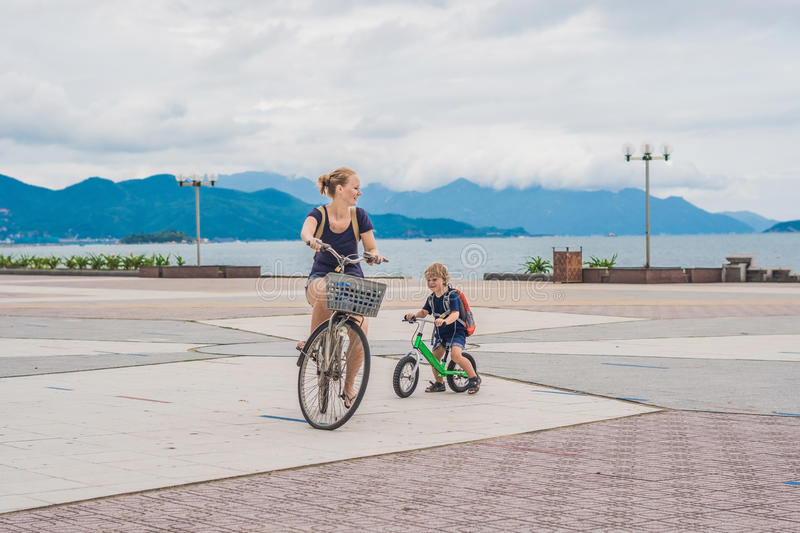 Happy family is riding bikes outdoors and smiling. Mom on a bike royalty free stock images