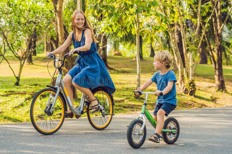 Happy family is riding bikes outdoors and smiling. Mom on a bike and son on a balancebike royalty free stock photos