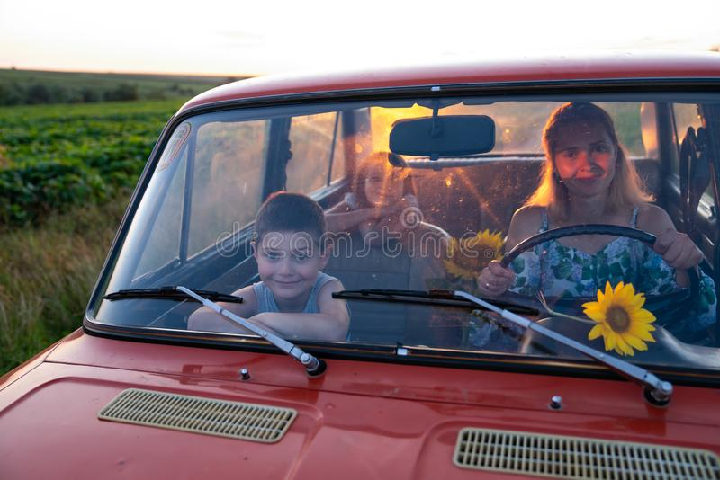 Happy family on a road trip in their car, young mother driving a red retro car with her teen children, enjoying stock photo