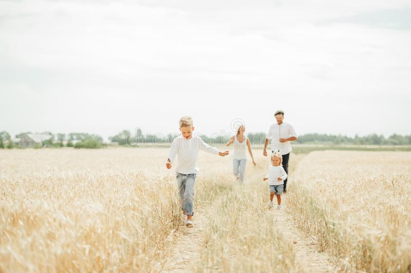 Happy family run in wheat field in sunny day. The concept of  healthy lifestyle, happiness and joy royalty free stock photography