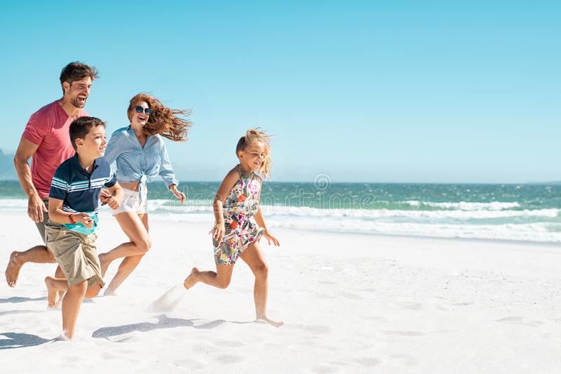 Happy family running on beach stock photography