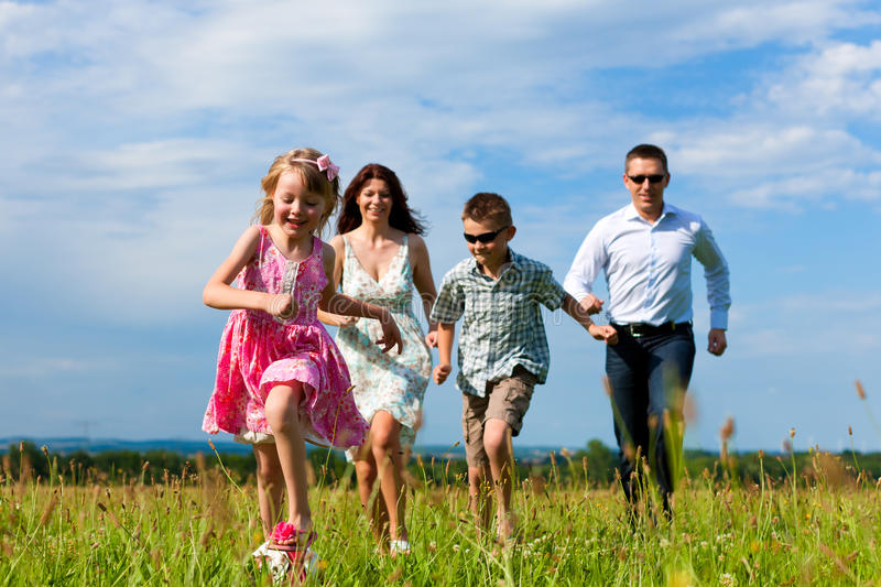 Happy family running on meadow in summer royalty free stock images