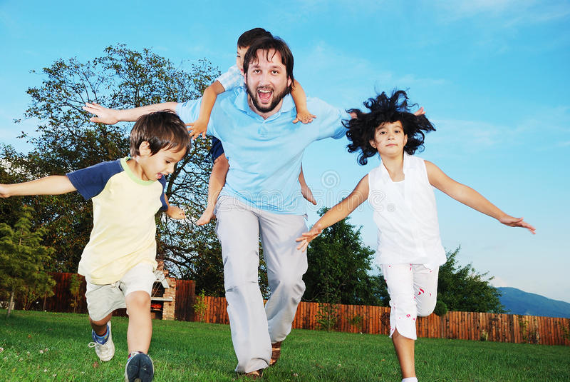 Happy family running outdoor, on beautiful garden stock photography