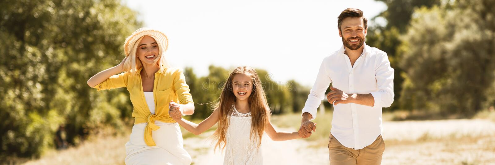 Happy family running together in countryside, panorama royalty free stock image