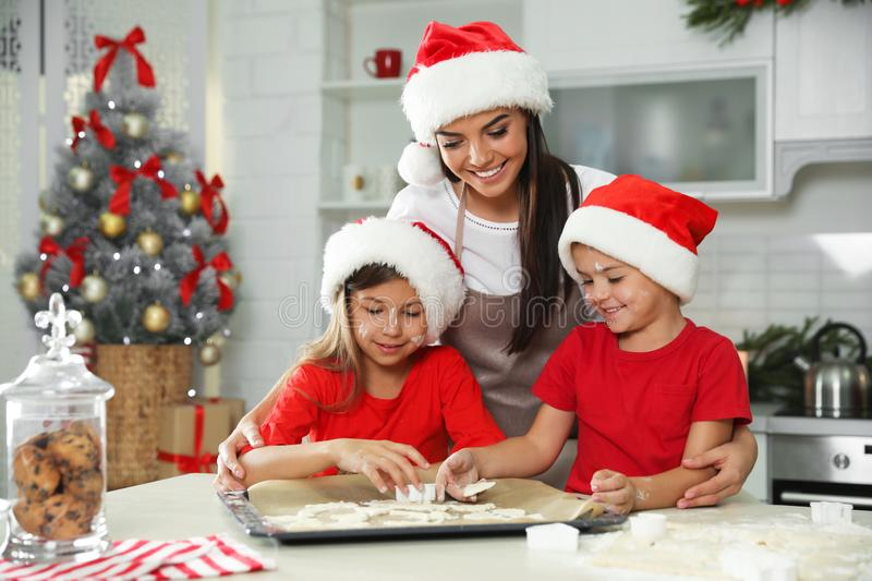 Happy family with Santa hats cooking. Christmas time. Happy family with Santa hats cooking in kitchen. Christmas time royalty free stock photos