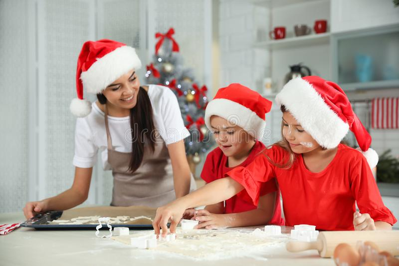 Happy family with Santa hats cooking in kitchen royalty free stock photos