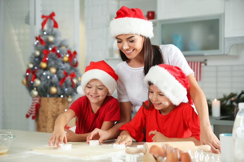 Happy family with Santa hats cooking in kitchen. Christmas time royalty free stock photo