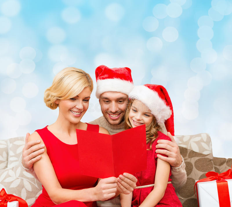 Happy family in santa hats with greeting card stock image