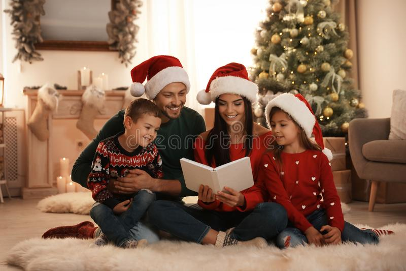 Happy family in Santa hats reading book on floor stock image