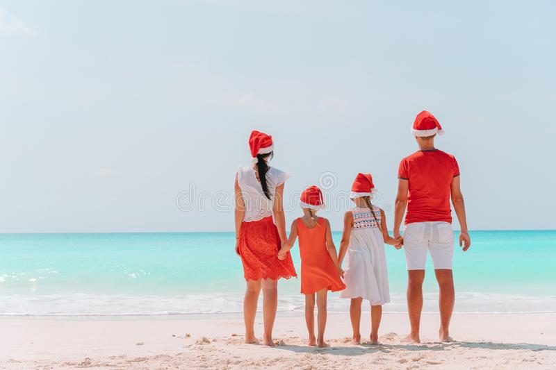Happy family with two kids in Santa Hat on summer vacation royalty free stock image
