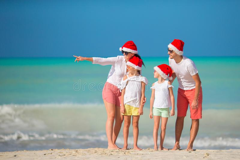 Happy family with two kids in Santa Hat on summer vacation. Happy family in Santa hats on a tropical beach celebrating Christmas vacation stock photo