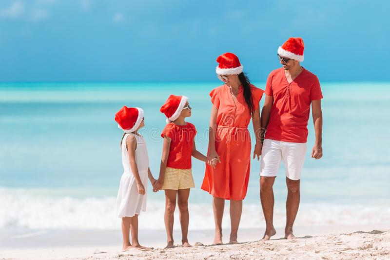 Happy family with two kids in Santa Hat on summer vacation. Happy family in Santa hats on a tropical beach celebrating Christmas vacation stock image
