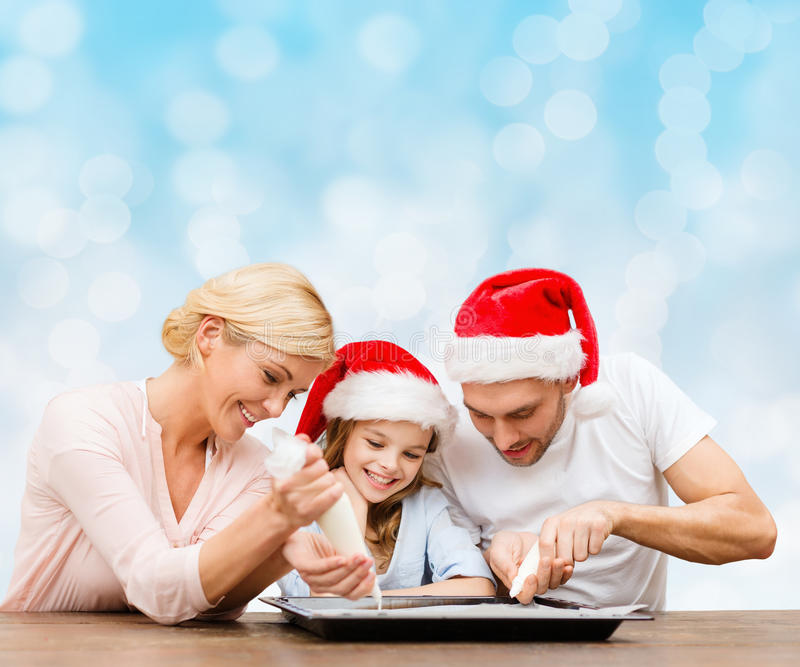 Happy family in santa helper hats cooking royalty free stock images