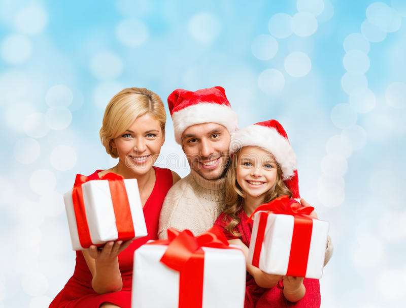 Happy family in santa helper hats with gift boxes. Christmas, holidays, family and people concept - happy mother, father and little girl in santa helper hats stock images