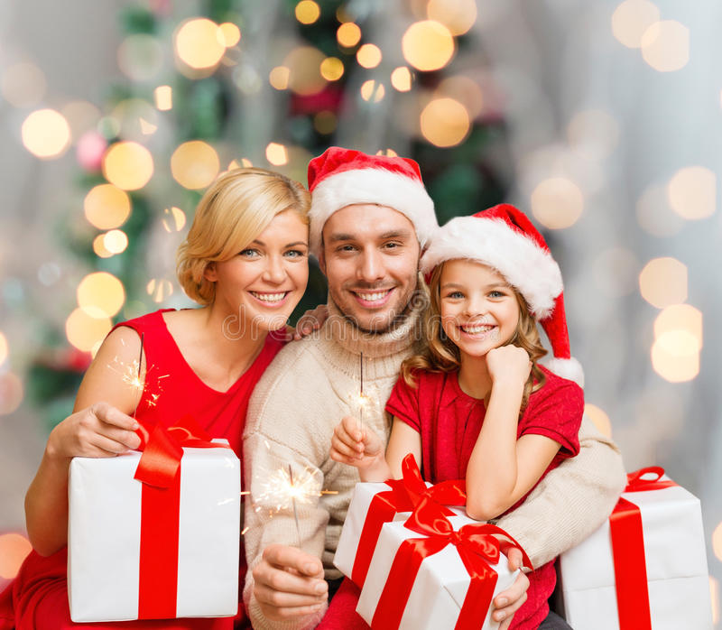 Happy family in santa helper hats with gift boxes. Christmas, holidays, family and people concept - happy mother, father and little girl in santa helper hats royalty free stock images