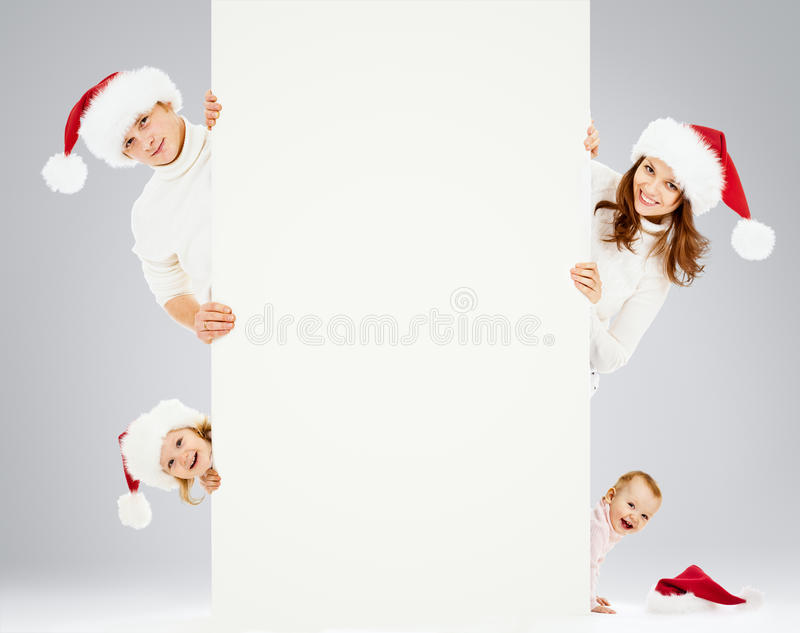 Happy family in Santa's hats waiting Christmas stock images