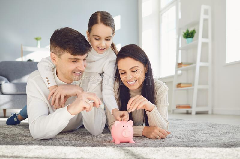 Happy family saves money in a piggy bank pig. Money finance saving concept stock photography