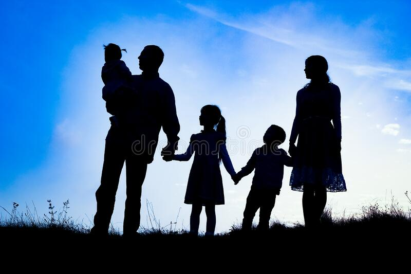 Happy family by the sea on nature silhouette background stock photos