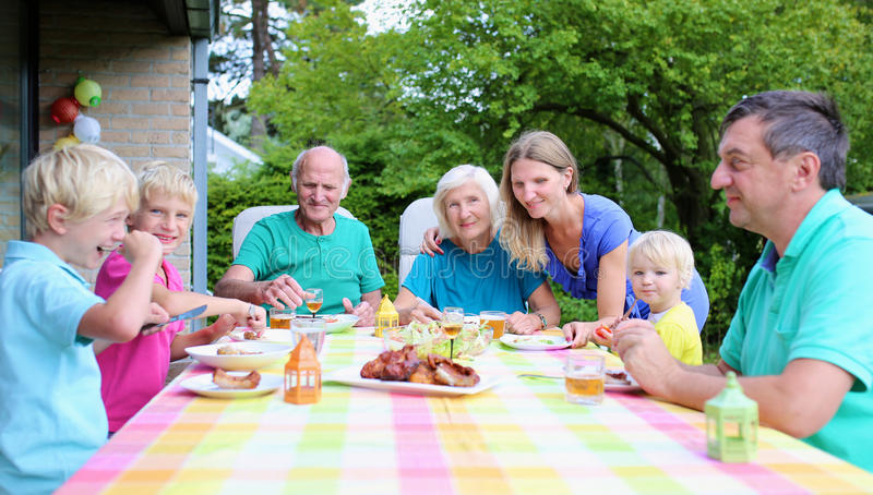 Happy family of seven having meal together royalty free stock photography