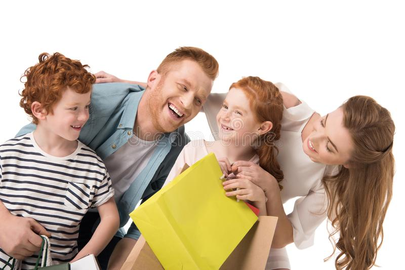 Happy family with two kids holding shopping bags. Isolated on white stock images