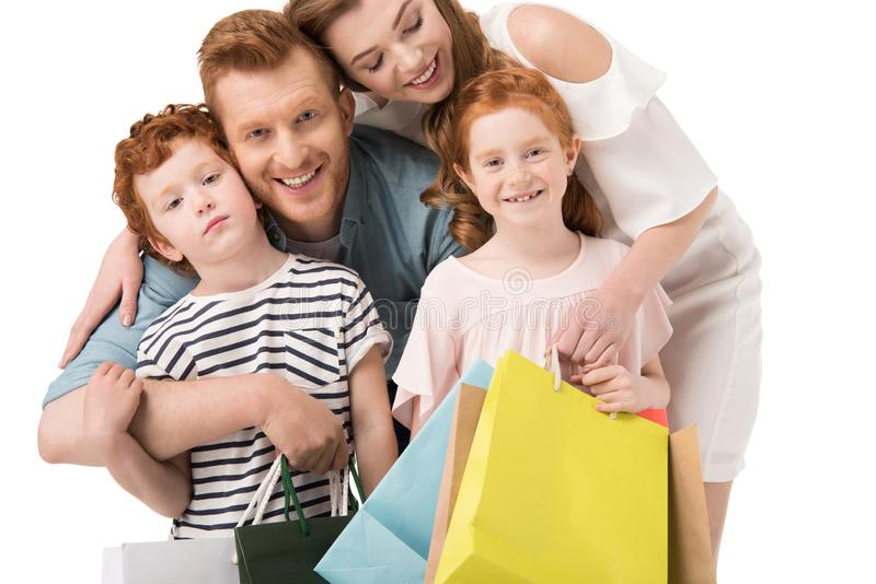Happy redhead family holding shopping bags and smiling at camera. Isolated on white royalty free stock images
