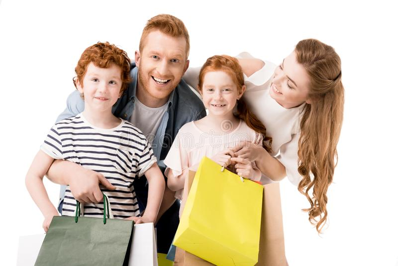 Happy young family holding shopping bags and smiling at camera. Isolated on white stock images