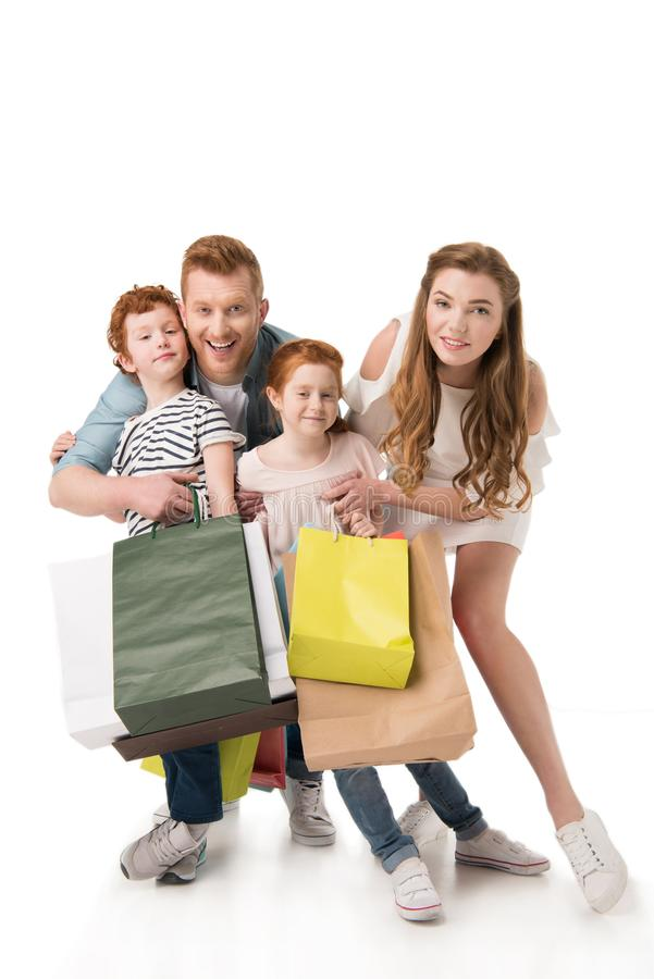 Happy young family with two children holding paper bags. Isolated on white royalty free stock image