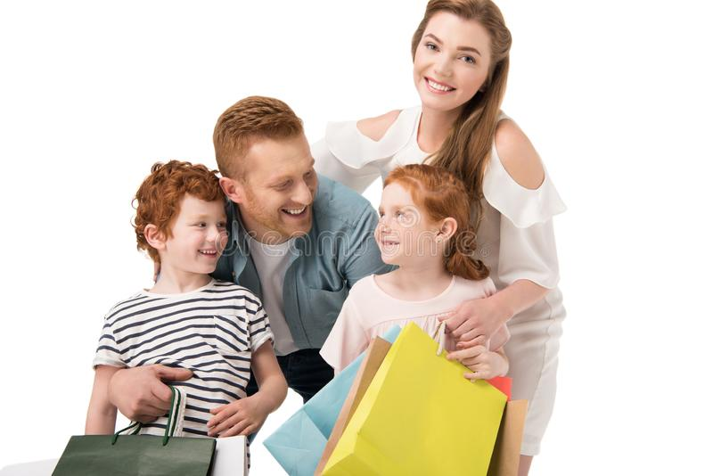 Happy young family with two children holding shopping bags. Isolated on white royalty free stock photo