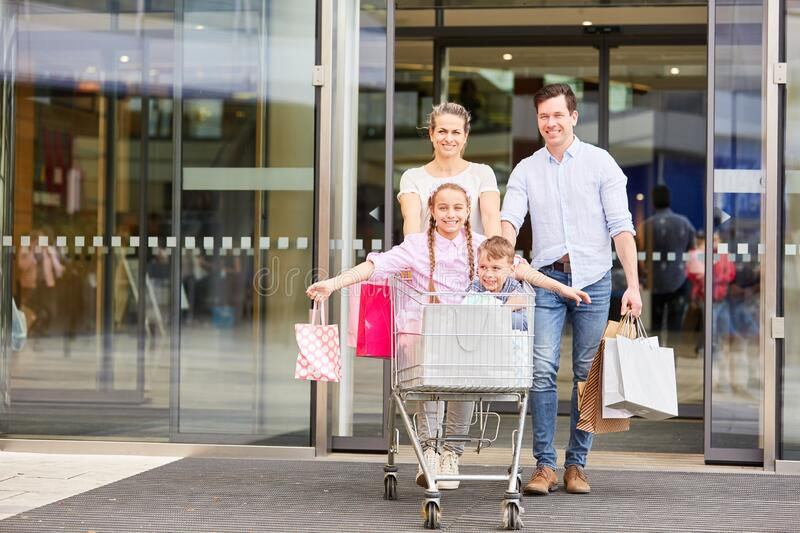 Happy family after shopping. With shopping cart and shopping bags royalty free stock image