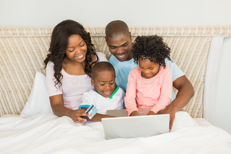 Happy family shopping online with laptop. On bed stock image