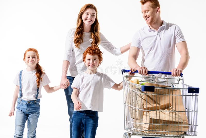 Happy redhead family with shopping trolley walking together. Isolated on white stock photography