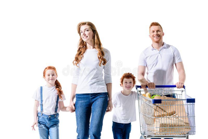 Happy young family holding hands and walking with shopping trolley. Isolated on white royalty free stock images