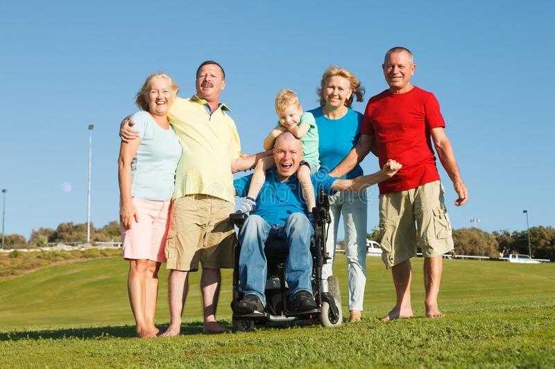 Happy family showing unity. Disabled men with family outside showing unity stock photography