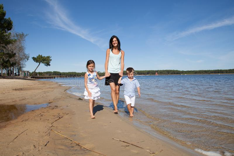 family of single mother, and two child, son daughter walking holding hands in the sea sand of a sunny beach stock photography