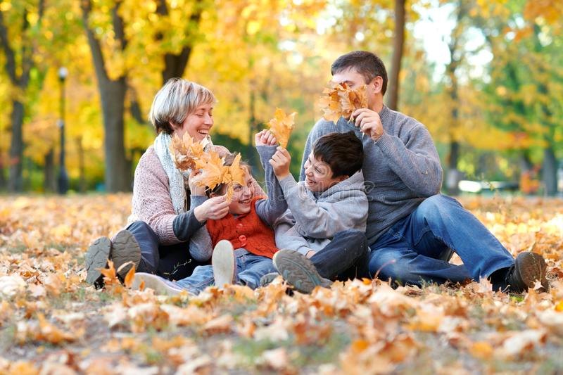 Happy family sit in autumn city park on fallen leaves. Children and parents posing, smiling, playing and having fun. Bright yellow royalty free stock photos