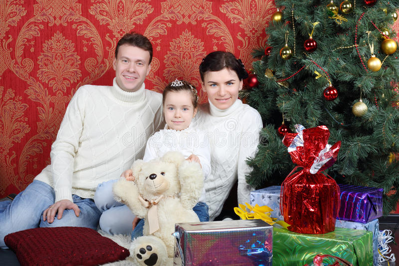 Happy family sit on floor with gifts near Christmas tree. At home stock photo